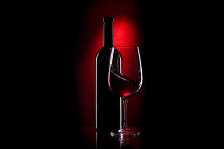 Glass and bottle of red wine on a dark red background Banque d'images - 124901289