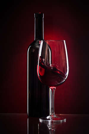 wine glass and bottle of red wine on a dark red background
