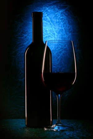 glass of red wine and wine bottle on blue stone background, drink against the wall in the old cellar Imagens