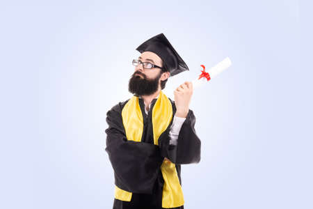 graduated man holding diploma over blue background serious face thinking about question, very confused idea