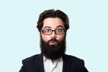 Wow! Surprised bearded businessman in glasses with open mouth, close up portrait Imagens