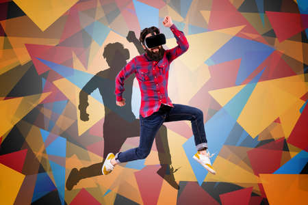 full length portrait of young bearded hipster man in virtual reality glasses, jumping over colored background with geometric elements Фото со стока