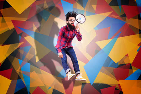 Bearded hipster man in glasses, jumping and shouting in megaphone, photo over colored background with geometric elements 스톡 콘텐츠