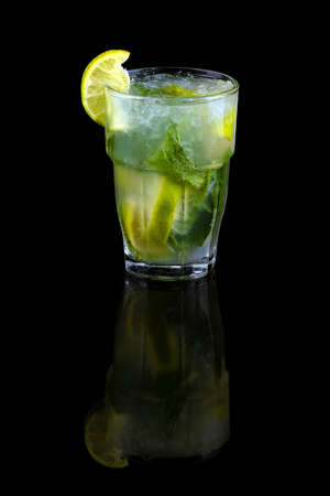 mojito cocktail with lime, mint leaves and ice cubes, refreshing summer drink over black background