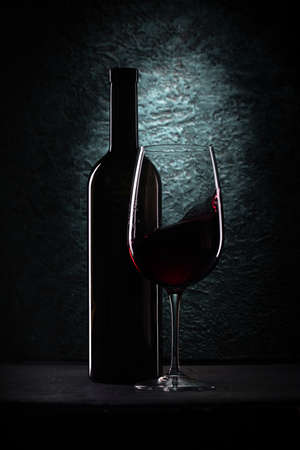 Red wine glass and bottle on azure stone background, drink against the wall in the old cellar Banque d'images - 124901712