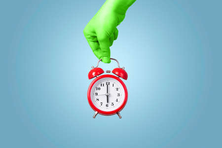 red alarm clock in green hand, over blue background, concept time to get up Stock Photo