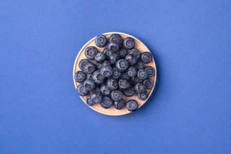 Ripe blueberries in the wooden bowl. Top view, summer berries on a blue background