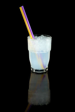 coconut water with ice cubes, concept summer cool drink with a straw, over black background