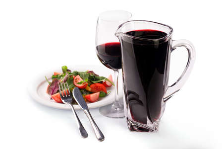 Pitcher with red wine and salad of lettuce, tomatoes and cucumbers in a plate, isolated on white background