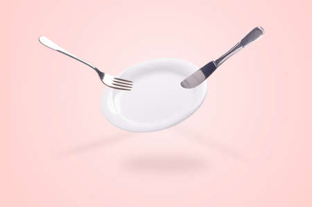 levitating empty plate with knife and fork over pink background, clean kitchenware concept Stock Photo