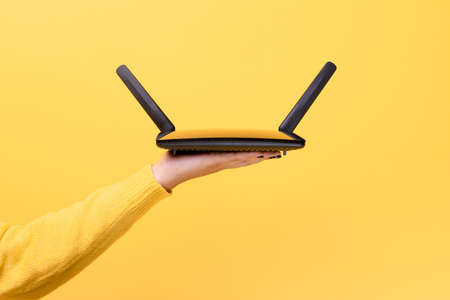 black wifi router on female hand over yellow background