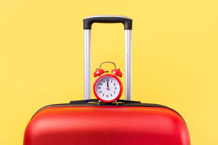 Travel case with alarm clock over yellow background. Time to voyage. Voyage concept. Retro alarm clock with red suitcase