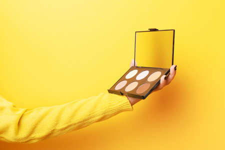 Eyeshadows and correctors, a large palette of make-up artist in hand over yellow background. Makeup Accessories