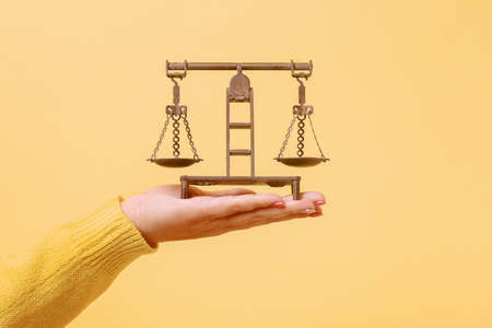 bronze antique scales on hand over yellow background, symbol of justice