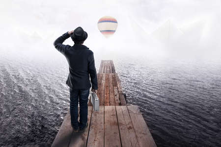 Back view of a man in black hat, standing on wooden pier and looking into the distance at paper boats and colorful air balloon. Concept of dreams and imagination. Stockfoto
