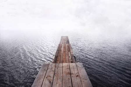 front view of wooden pier going into the water and fog, 
