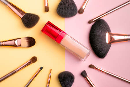 Makeup products and cosmetic brushes with fondation on multi color background, flat lay. Fashion and beauty blogging concept. Top view 写真素材