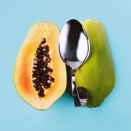 Half sliced papaya and dessert spoon on blue background, vegetarian food concept.