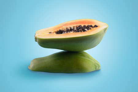 half sliced green papaya on blue background, balance concept 写真素材