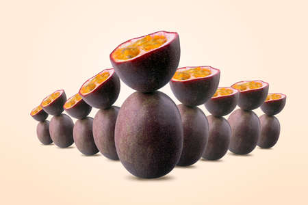 group of half sliced passion fruits balancing on whole passion fruits on peach background