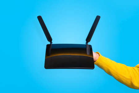 black wifi router on hand over blue background