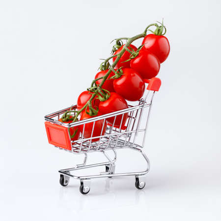 Mini shopping cart with cherry tomatoes on light gray background, shallow DOF.