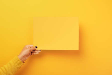 piece of paper in the female hand over yellow trendy background, empty blank for advertisement