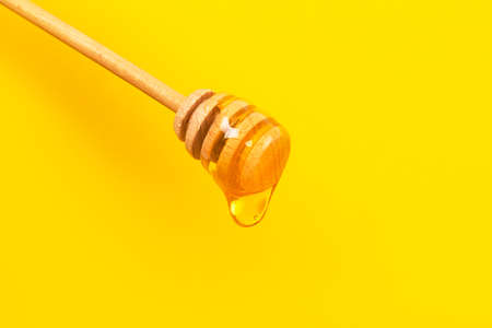 Honey dripping from honey dipper on yellow background. Thick honey dipping from the wooden honey spoon. Healthy food and diet concept