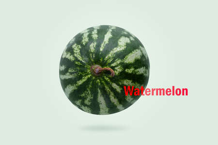 Levitating watermelon with red Watermelon inscription on light green background 写真素材