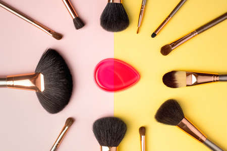 Makeup products and cosmetic brushes with sponge on multi color background, flat lay. Fashion and beauty blogging concept. Top view 写真素材