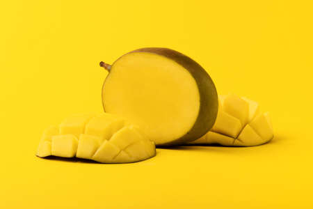 mango fruit with mango sliced cubes on yellow background