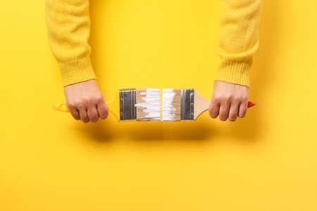 Paint brush in the hand of a girl on a yellow background, concept of apartment repair and painting works 写真素材 - 132105980