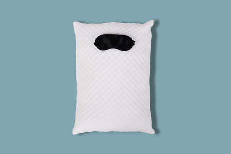 Personofied white quilted pillow with sleeping mask on blue background. Soft cushion for comfortable sleep and sweet dreaming