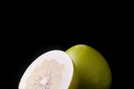 One pomelo and half sliced pomelo fruit on black background 写真素材