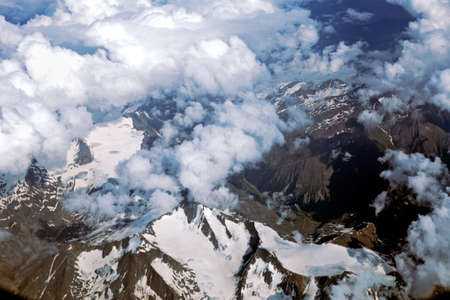 Alps and clouds from the plane. Earth through the porthole. Aerial view, concept of flight trip 写真素材