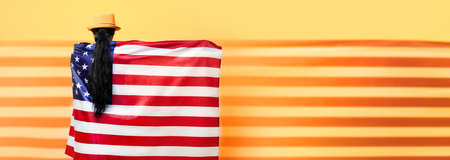 girl stands with her back and holds the American flag over yellow background, girl in fashionable hat with USA flag, panoramic mock up image