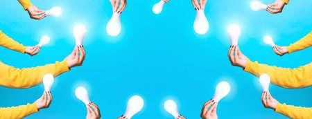idea solar energy, hands holding light bulbs, illuminated light bulbs over blue background, panoramic image