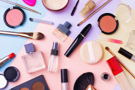 Makeup products and decorative cosmetics on multi color background, flat lay. Fashion and beauty blogging concept. Top view 写真素材
