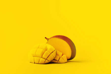 mango fruit with mango sliced cubes on yellow background with space for text. 写真素材