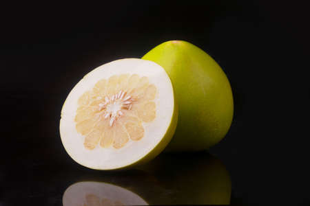 One pomelo and half sliced pomelo fruit on black background with reflection