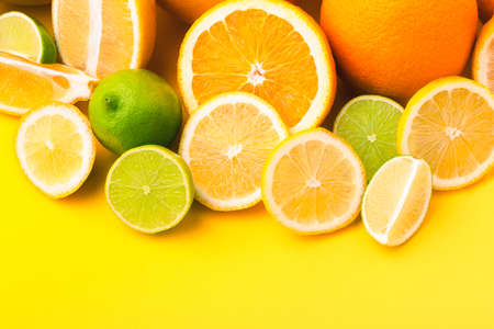 Citrus fruits (orange, lemon, grapefruit, lime) on yellow background. Summer concept. Set of tropical fruits 写真素材