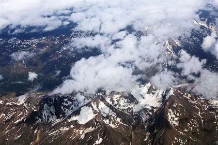 Alps and clouds from the plane. Earth through the porthole. Aerial view, concept of flight trip Zdjęcie Seryjne