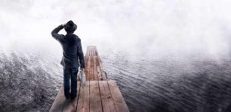 Vue arrière d'un homme au chapeau noir, tenant une analyse de rentabilisation, debout sur une jetée en bois et regardant au loin. En attente et à la recherche d'un concept d'idée d'entreprise.
