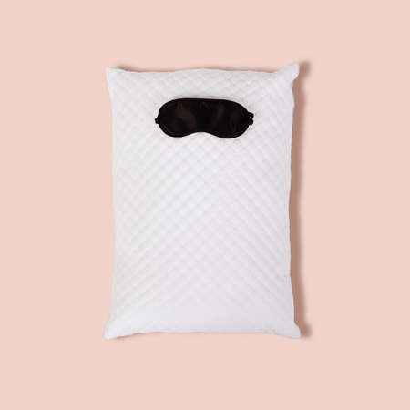 Personofied white quilted pillow with sleeping mask on pink background. Soft cushion for comfortable sleep and sweet dreaming