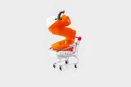 orange sliced paprika pepper in a shopping cart on gray background,  concept of 3d modelling Zdjęcie Seryjne