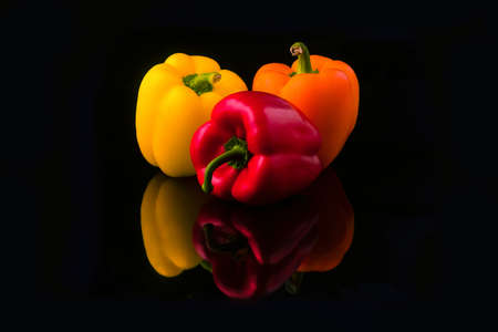 yellow, red and orange pepper paprika on a black background