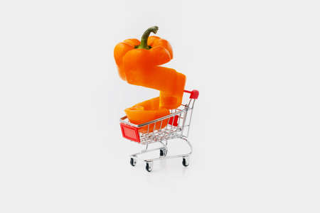 orange sliced paprika pepper in a shopping cart on gray background, vegetable purchase concept Zdjęcie Seryjne