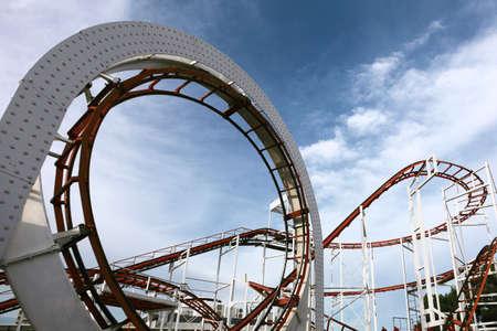 roller coaster track, childrens carousel on a background of blue sky Zdjęcie Seryjne