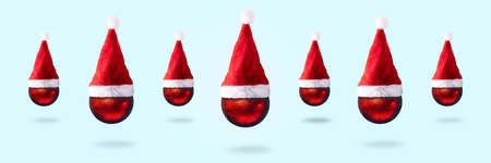 christmas red balls in santa claus hats over blue background, merry christmas concept, panoramic image