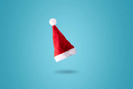 Creative Santa Claus hat over blue background. Minimal winter flat lay Christmas concept. Merry Christmas